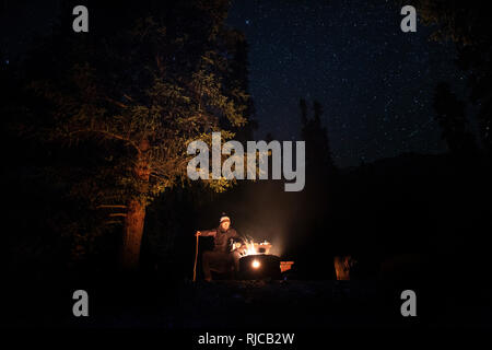 Alberta, Jasper National Park, Kanada, Kanadische Rocky Mountains, Mann sitzt am Feuer im Wilcox Creek Campground - Stock Image