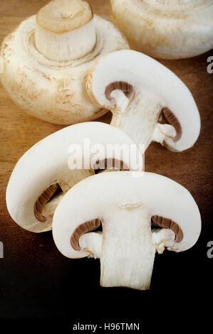 fresh champignon mushrooms on wooden background - Stock Image
