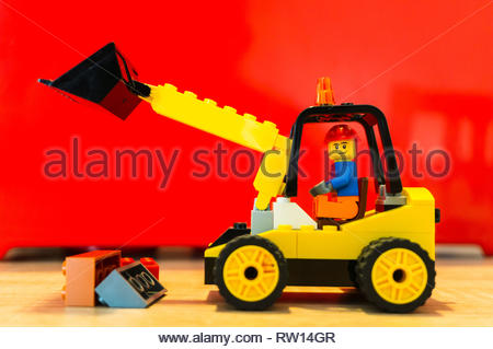 Poznan, Poland - February 15, 2019: Lego construction worker moving bricks with a excavator. - Stock Image