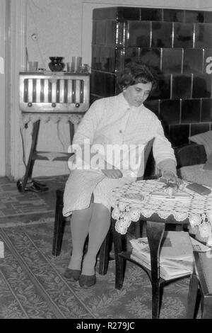 mature female sitting in living room at table with vintage radio and large ceramic wood burner in background 1960s hungary - Stock Image