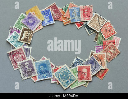 Collection of very old european postage stamps in oval frame, isolated on grey background - Stock Image