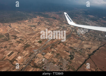 view showing the wing tip of a ryanair passenger Boeing 737 jet flying over Spain - Stock Image