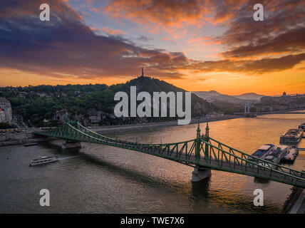 Budapest, Hungary - Aerial skyline view of a beautiful sunset over River Danube and Gellert Hill with sightseeing boat, Liberty Bridge, Buda Castle an - Stock Image