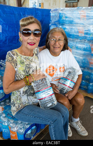 Women come to collect water from a water charity in Porterville supplying bottled water to houses who have had no - Stock Image