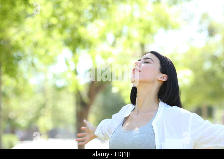 Woman relaxing in a park breathing deeply fresh air with a green background - Stock Image