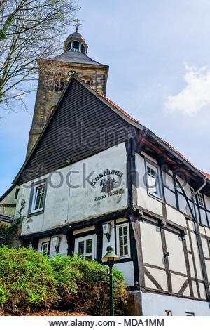 Post-and-beam (Fachwerk) Gasthaus Anno 1560 with the bell tower of die evangelisch Stadtkirche in the center of Tecklenburg - Stock Image