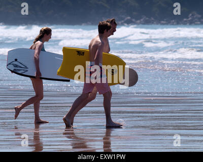 Father and teenage children heading for the sea with bodyboards, Woolacombe, Devon, UK - Stock Image