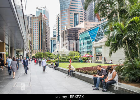 Singapore - 21st December 2018: People in Raffles Place. The garden is in the centre of the business district. - Stock Image