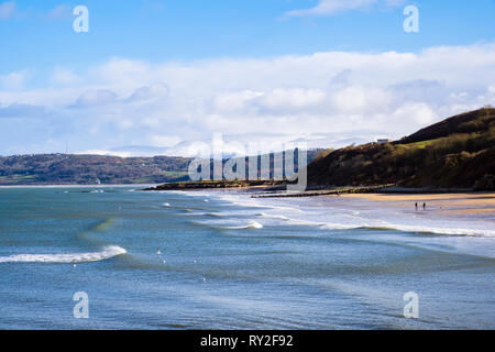 View across Benllech Bay and beach in sunshine with snow on distant mountains of Snowdonia. Benllech, Isle of Anglesey, North Wales, UK, Britain - Stock Image
