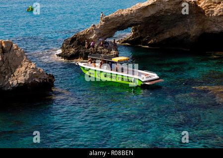Glass bottom fishing boat at The Love Bridge arch, Ayia Napa, Cyprus October 2018 - Stock Image