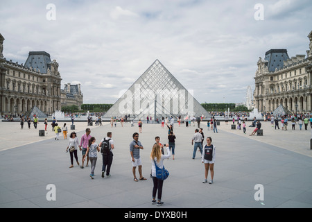 View of the Louvre Pyramid amidst tourists in the city of Paris, France. - Stock Image