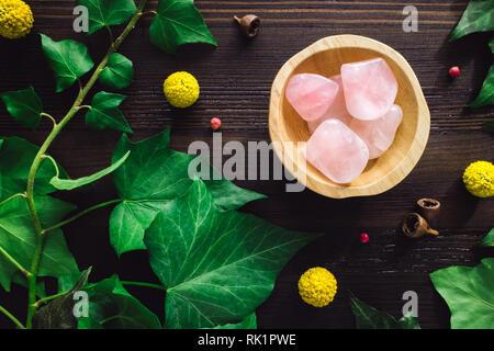Polished Rose Quartz with Ivy and Craspedia on Dark Wood - Stock Image