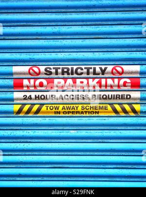 A blue roller shutter door cover d in warning signs that advise No Parking is permitted in this area. Constant access is required to this building. Your vehicle will be removed. You have been warned! - Stock Image