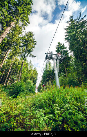 Mountain lift on a green forest with tall pine trees in the summer - Stock Image