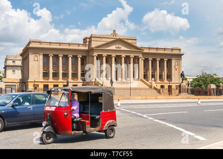 Colombo, Sri Lanka - March 16th 2011: A car and tuk tuk drive past the old parliament building. The architecture is neo baroque style. - Stock Image