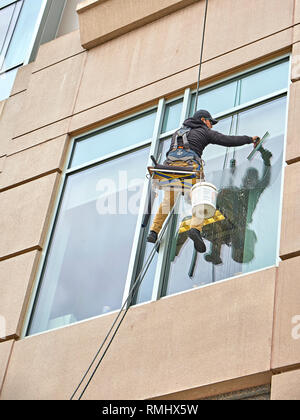 Close up of a window washer cleaning the outside windows of a high rise building from a low angle, in Montgomery Alabama, USA. - Stock Image