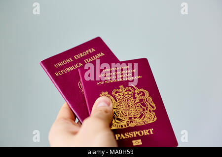 Male hand extending to present British passport stacked on top of Italian passports, on grey background. - Stock Image