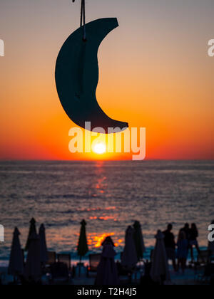 Sunrise in Thasos with focus on the model moon - Stock Image