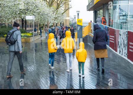 Three children walking along the Southbank in London and wearing matching bright yellow jackets in the rain. - Stock Image