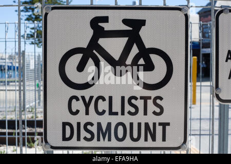 Sign at a railway crossing requesting that cyclists dismount before crossing. - Stock Image