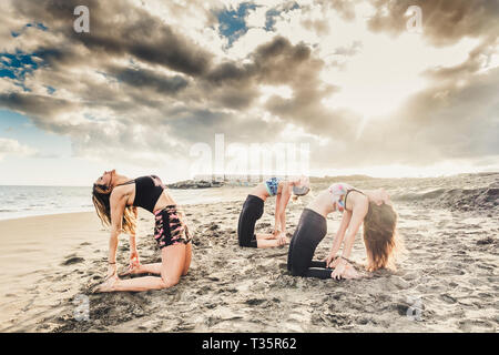 Scenic colors and background for Pilates and yoga healthy sport fitness activity at the beach with three young girls doing plank on the sand with blue - Stock Image