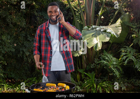A man barbecuing vegetables and talking on a cellphone - Stock Image