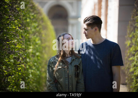 A young couple traveling. Standing on the street and looking at each other. Mid shot - Stock Image