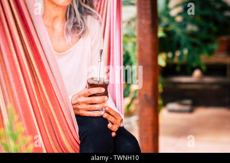 Close up of natural healthy alternative yoga caucasian woman drinking nature tea sitting on an hammock to relax and enjoy outdoor relax leisure activi - Stock Image
