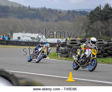 East Fortune, UK. 14 April, 2019. 144 Keith Shepherd leads 87 Jodie Chalk through Hannah's in a CB500 race at East Fortune Raceway, during the opening rounds of the 2019 Scottish Championships, Melville Open and Club Championships. Credit: Roger Gaisford/Alamy Live News - Stock Image