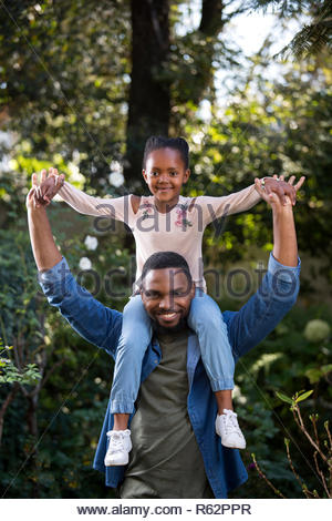 A young girl sitting on her fathers shoulders - Stock Image