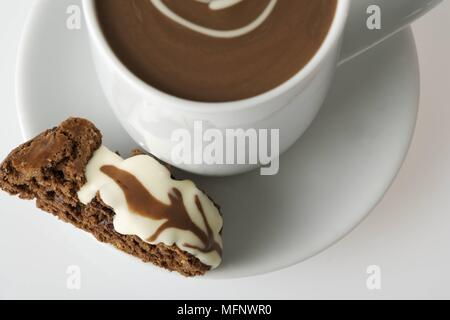 White porcelain cup with drinking chocolate. Almond and chocolate biscoti in saucer. Studio shot.      Ref: CRB538_103609_0012  COMPULSORY CREDIT: Mar - Stock Image