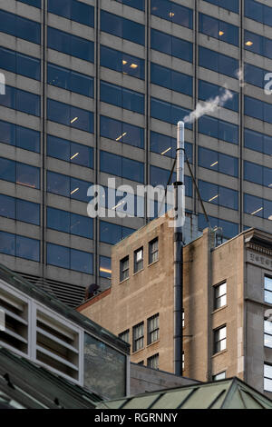 Steaming chimney near Post Office Square at top of 24 Federal Street Building. Shot on freezing day in Boston, showing behind is One Federal Building. - Stock Image