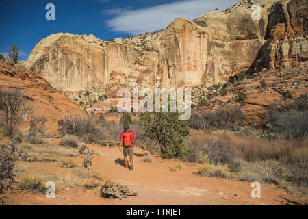Rear view of hiker with backpack walking on desert against rock formations - Stock Image