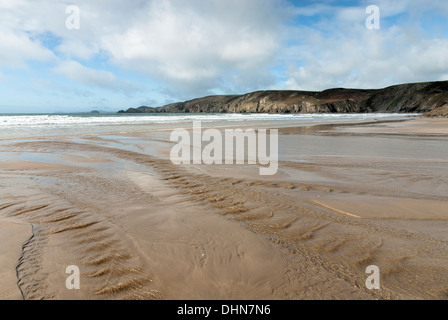 Deserted Newgale Sands Beach with freshwater stream water flowing to the sea and with cliffs and surf in the background. - Stock Image