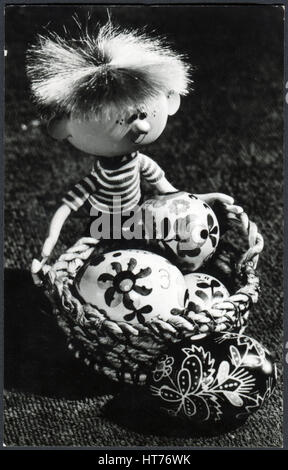 HUNGARY - CIRCA 1970: A greeting Easter postcard printed in Hungary, shows a toy with a basket of Easter eggs, circa - Stock Image