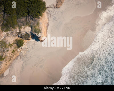 Aerial drone view at a beach section of Riviera Nayarit, Mexico, with a woman lying on her back tanning. - Stock Image