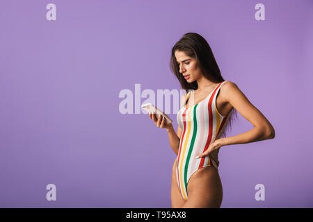 Confused young girl wearing swimsuit standing isolated over violet background, talking on mobile phone - Stock Image