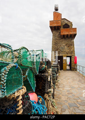 Lobster pots in front of the Rhenish Tower on the wall of Lynmouth Harbour, Devon, England, UK - Stock Image