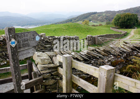 Public bridleway with sign pointing in the direction of Skelghyll, Jenkin Crag and Ambleside in the Lake District. Windermere visible at upper left - Stock Image