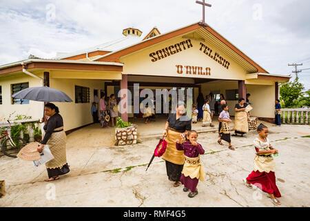 Polynesian parishioners in traditional Tongan dress walk out of church as Catholic Mass ends,  Pangai village, Ha'apai Group in Tonga, Polynesia. - Stock Image