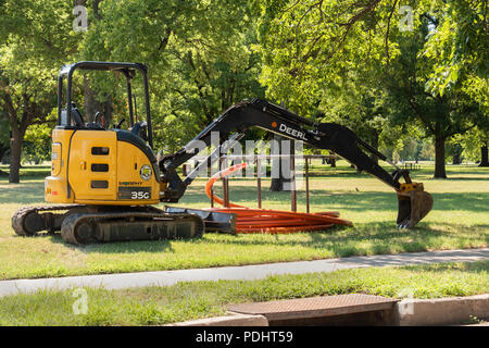 A John Deere backhoe parked and idle during the summer in the USA. - Stock Image