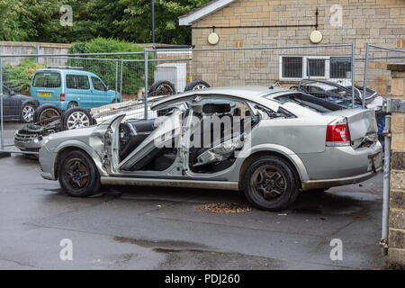 A Vauxhall Vectra that has had the doors removed and roof cut off for training sat outside a firestation - Stock Image