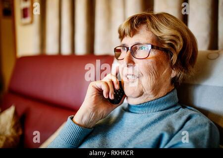 Senior citizen telephoning in her living room, North Rhine-Westphalia, Germany - Stock Image