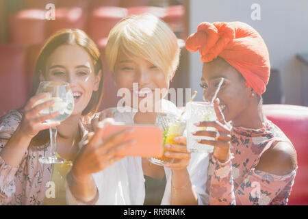 Young women friends drinking cocktails and taking selfie with smart phone in sunny bar - Stock Image