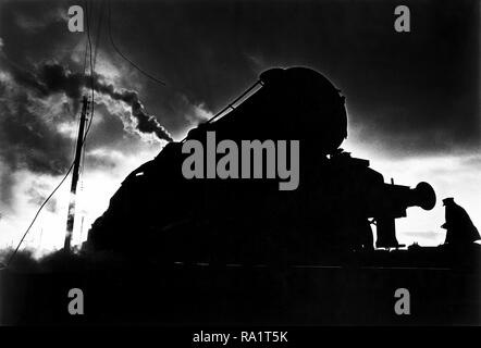 August 1968, the last month of steam railways in Britain. Carnforth, Lancashire, near Lancaster. An engine driver walking up the tracks to begin a late turn, driving a night train. - Stock Image