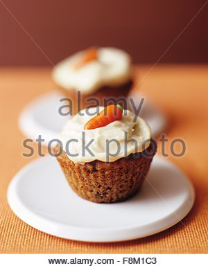 Carrot Cake Cupcakes with Candy Carrot Decoration - Stock Image