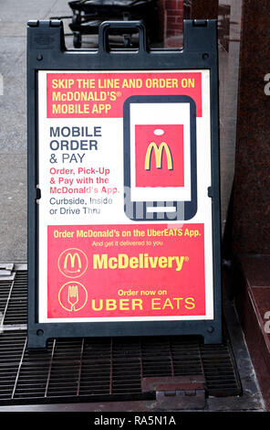 A sign outside a McDonald's in Greenwich Village promoting a new mobile app and the ability to order on McDelivery and Uber Eats. - Stock Image