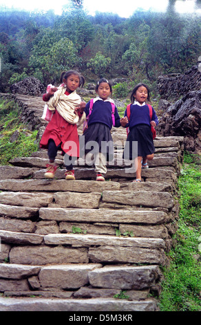 Three little girls from Primary School running down stone staircase near Chomrong on Annapurna circuit Nepal Himalaya - Stock Image