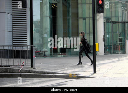 Stylish young woman wearing black walking along Finsbury Pavement outside a corporate building in the City of London - Stock Image