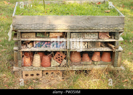 Bug hotel made of bricks and plant pots - Stock Image